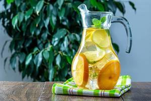 Hausgemachte Limonade mit Eiswürfeln, Zitronenscheiben und Minze in Karaffe auf Holztisch