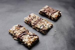 Hausgemachte Müsliriegel mit Schokolade auf schwarzem Hintergrund