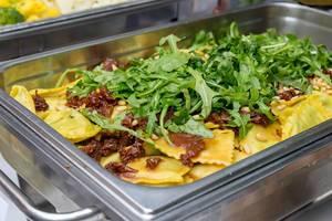 Hausgemachte Ravioli mit Spinat gefüllt, dazu getrocknete Tomaten Pinienkerne und Rucola an einem Buffet