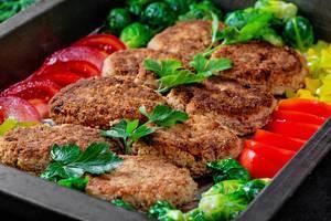 Hausgemachte Schnitzel aus Fleisch, auf einem Backblech, neben Gemüse und Kräutern