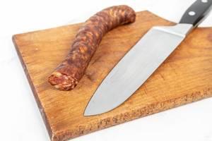 Hausgemachte Wurst aus heimischem Schweinefleisch, neben einem Küchenmesser