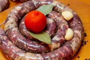 Hausgemachte Wurst und Zutaten wie Tomaten, Knoblauch, Pfefferkörnern und Lorbeerblättern