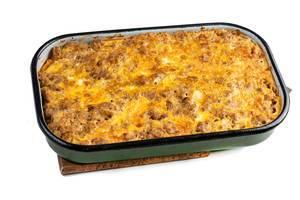 Hausgemachter Hackfleisch-Kartoffel-Auflauf mit Käse überbacken, in grüner Auflaufschale auf weißem Untergrund