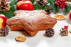 Hausgemachter sternförmiger Biskuitkuchen auf Weihnachtshintergrund