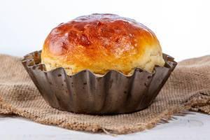 Hausgemachtes, rundes Brot in der Backform, auf einem Leinentuch