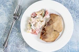 Hausgemachtes serbisches Gericht aus Schweinefleisch und Schopska-Salat aus Gemüse