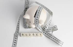 Haushaltsplan: Sparschwein mit Maßband und Buchstabenwürfeln welche das Wort