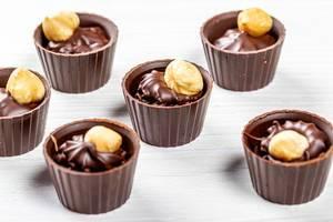Hazelnut and milk chocolate candies on white wooden background