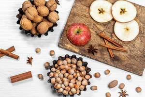 Hazelnuts, walnuts, cinnamon sticks, anise and apples on white wooden background