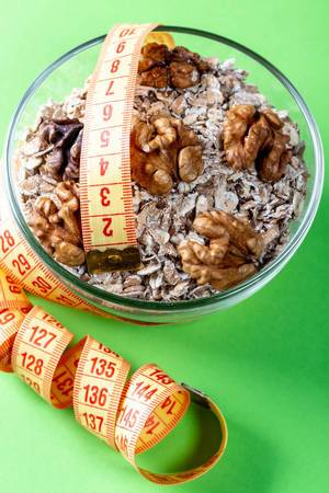 Healthy breakfast oatmeal with nuts and measuring tape