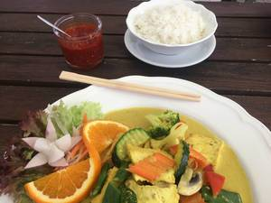 Healthy curry turmeric as vegan lunch, with rice, hot sauce, vegetables and salad, on a white plate with chopsticks