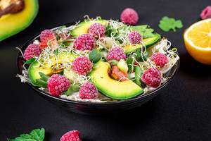 Healthy diet. Salad with raspberries and vegetables on a dark background (Flip 2020)