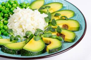 Healthy food concept- rice with vegetables and sunflower microgreen on a blue plate