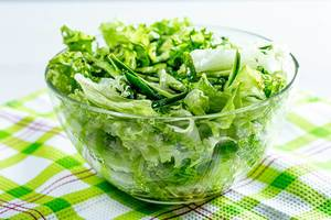 Healthy food. Fresh green salad with lettuce, cucumbers and herbs (Flip 2019)