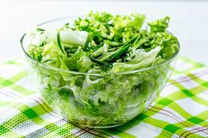 Healthy food. Fresh green salad with lettuce, cucumbers and herbs