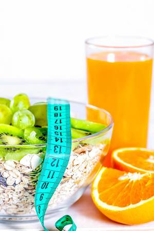 Healthy food: fresh orange juice, an orange cut in pieces, a bowl with muesli, kiwi and grapes and a measuring tape