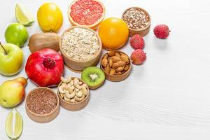 Healthy food ingredients. Fruits, nuts, seeds on wooden white background (Flip 2019)