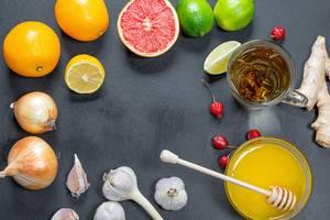 Healthy Food um das Immunsystem zu stärken mit Zitrusfrüchten, Grüntee, Ingwer, Wurzelzwiebel und Knoblauch auf schwarzem Hintergrund