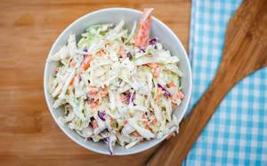 Healthy garnish: coleslaw in a white bowl on a wooden kitchen table