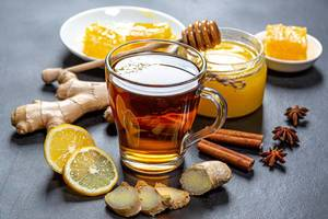 Healthy tea with ginger, honey, lemon and spices on black background
