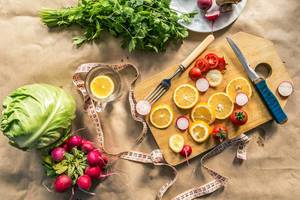 Healthy vegan food background with cutting board and lemon slices