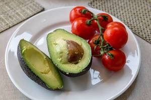 Healthy vegetable snack made of halved avocado and small tomatoes