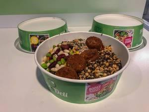 Healthy, vegetarian Picadeli salad, with meatless vegetable balls made of tomatoes & basil, power grain mix and beans in a green to-go box