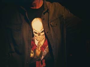 Heavy Metal Fan trägt Jeanshemd und Shirt mit großem Totenkopfmotiv und steht im Dunkeln