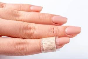 Heftpflaster um Finger von Frau gewickelt verbindet Wunde vor weißem Hintergrund