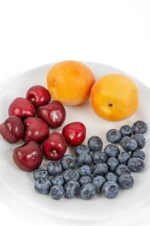 Heidelbeeren, frische Kirschen und zwei Aprikosen liegen gemeinsam auf einem Obstteller