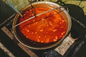 Heiße Tomatensuppe mit Fleisch in einem rustikalen Topf über einer Feuerstelle