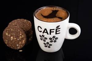 Heißer schwarzer Kaffee in stylischer Kaffeetasse neben Schokoladenkeksen isoliert vor schwarz