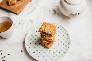 Helle Brownies auf Teller gestapelt mit Teekanne und Teetasse auf weißem Tischtusch