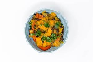 Hello Fresh - Caribbean stew made from sweet potatoes with black beans and coconut milk in a blue bowl on white background