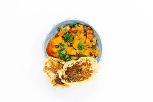 Hello Fresh - Carribian Sweet Potato Coconut Stew with Black Beans and Tasty Bananapancakes in blue bowl on white background - Top view