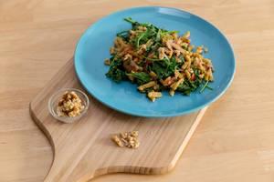 Hello Fresh - Herbstliche Grünkohl-Spätzle-Pfanne in cremiger Soße mit gerösteten Walnüssen auf einem blauen Teller auf einem Holzbrett