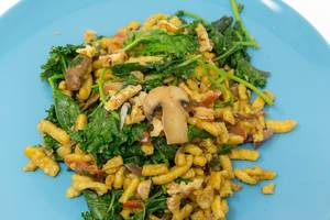 Hello Fresh Spätzle Noodles with kale and mushrooms in creamy sauce with roasted walnuts on a blue plate - close up
