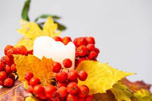 Herbstdekoration - Eine Kerze mit gelben Blätern und roten Beeren