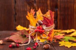 Herbstdekorationen  - Kerzenglas mit Laub und Eicheln geschmückt