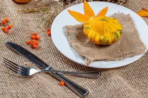 Herbstliche Darstellung zu Halloween und Thanksgiving mit Gedeck aus Teller und Besteck