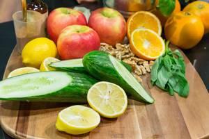 Herbstliche Kochzutaten: Frische Gurken, Äpfel, Nüsse und Zitrusfrüchte auf einem Holzbrett