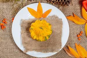 Herbstlicher Hintergrund mit bunten Blättern auf Leinen mit Kürbis auf weißem Teller im Zentrum