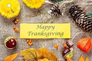 Herbstlicher Hintergrund mit Kastanien, bunten Blättern und Zweigen als Happy Thanksgiving Gruß