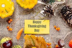 Herbstlicher Hintergrund mit Kastanien und bunten Blättern umgeben eine Happy Thanksgiving Day Schrift auf gelbem Papier