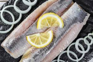 Herring fillet with onion and lemon on black stone. Top view