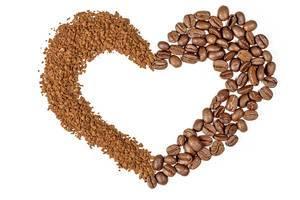 Herzförmiger Kaffee-Rahmen vor weißem Hintergrund. Aufnahme von oben