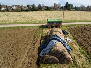 Heuhaufen zwischen bestellten Feldern und ein Anhänger im Hintergrund - Drohnenaufnahme