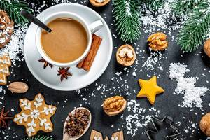 High angle shot of a cup of coffee, with christmas tree branches, cookies and nut in festive decoration