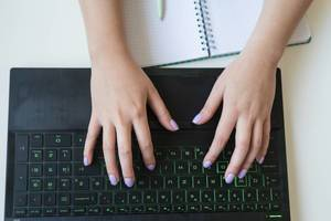 High angle shot of female hands typing on a laptop