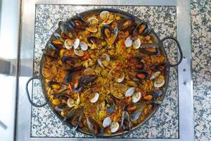 High angle view of paella with fresh mussels in a cast iron pan